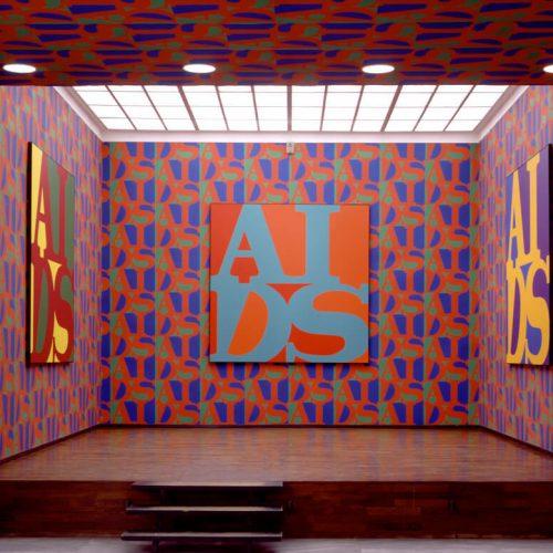 General Idea, installation intitulée AIDS, 1988-1990, consistant en trois tableaux AIDS, 1988, acrylique sur toile, 243,7 x 243,7 cm chacun, accrochés sur Papier peint AIDS, 1990, sérigraphie sur papier peint ; roulé : 68,6 x 4,6 cm (diam.), déroulé : 457 x 68,6 cm, dimensions d'ensemble variables, Musée des beaux-arts de l'Ontario, Toronto. Lieu : exposition General Idea's Fin de siècle, Württembergischer Kunstverein, Stuttgart, Allemagne, 1992.